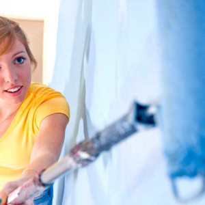 Young woman painting a wall - Wand streichen blau