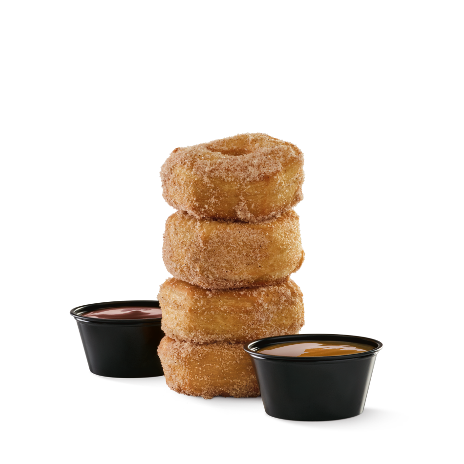Four cinnamon and sugar croissant donut rings served with caramel and fudge.