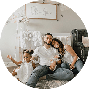 Dr. Brittney J. Fusilier pictured with her family in her newborn's nursery.