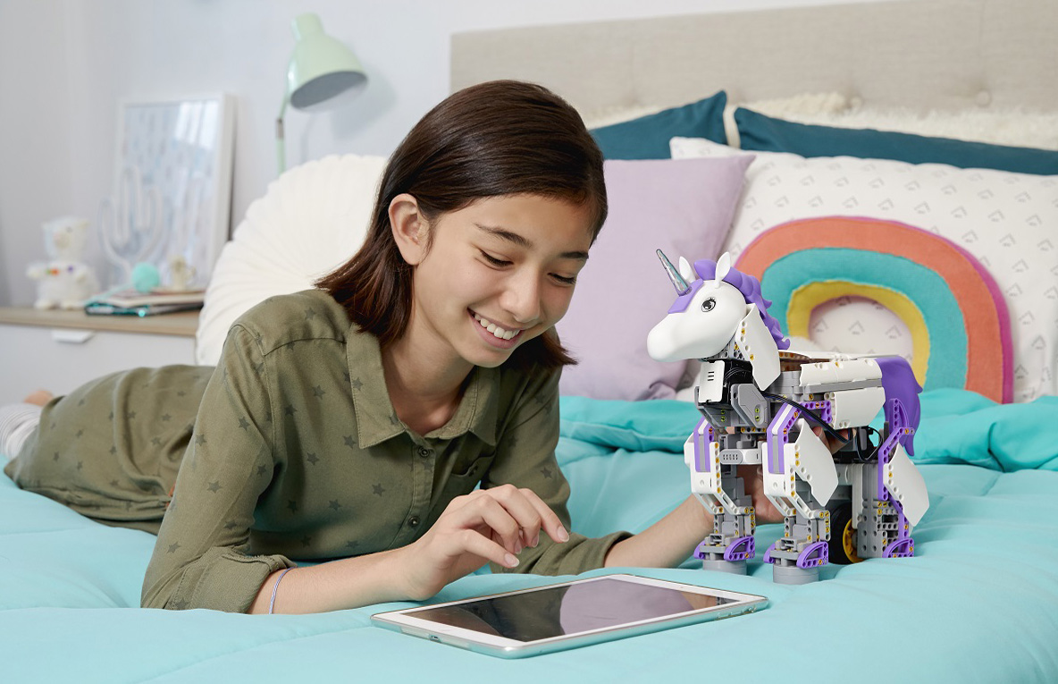 Young girl in bedroom programming UnicornBot