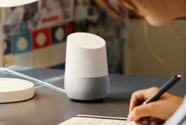 Woman Writing in Notebook with Google Home on Desk