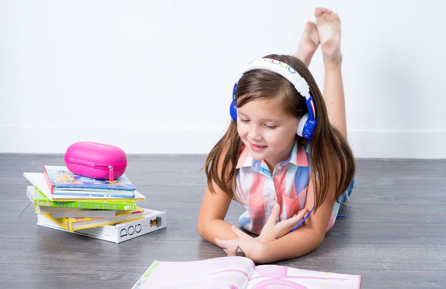 Young girl wearing blue BuddyPhones and reading