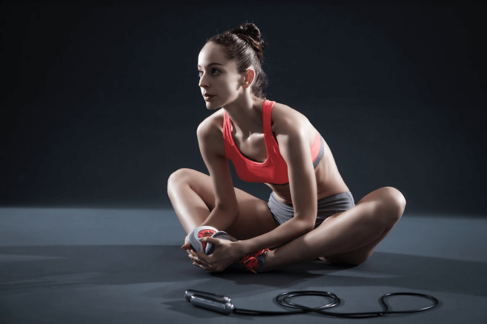 Woman Stretching Beside Chrome Tangram Jump Rope