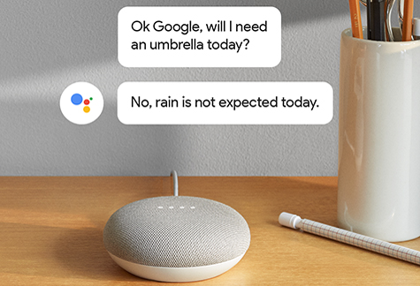 Google Home Mini on a desk with speech bubbles