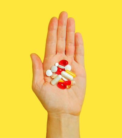 Palma de uma mão feminina com dezenas de comprimidos coloridos sobre fundo amarelo.
