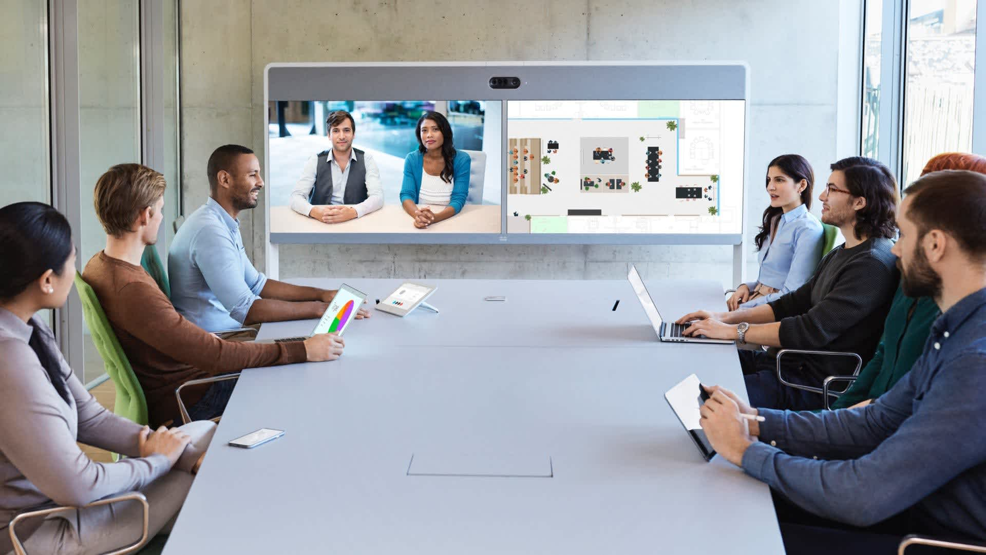 7 people around a conference table in a video meeting with a two other people through a Cisco Webex Room 70 Dual G2