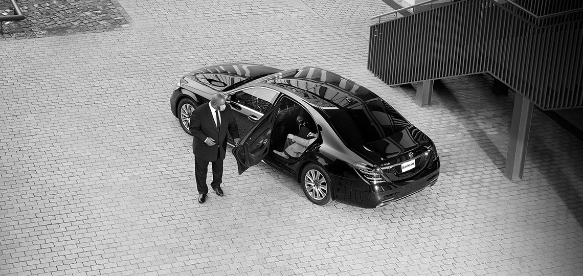 A view from above of a plaza where real Blacklane chauffeur Jeffrey opens the door to let the guest out of the back seat while wearing a mask.