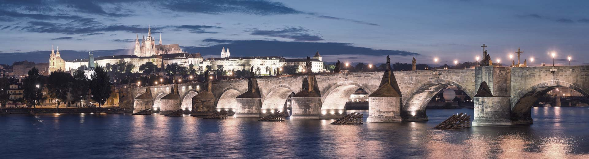 The famous Charles Bridge in Prague is deftly illuminated under a sky of dusk or dawn, with historic spires in the background