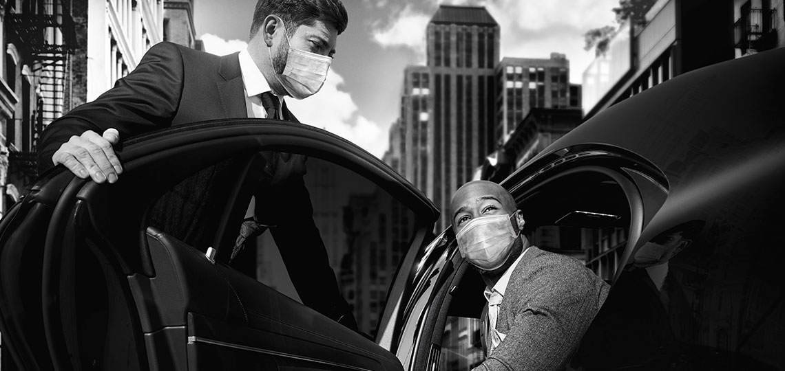 A Blacklane chauffeur wearing a mask opens the door of his Mercedes to le the guest, also wearing a mask, out of the vehicle.