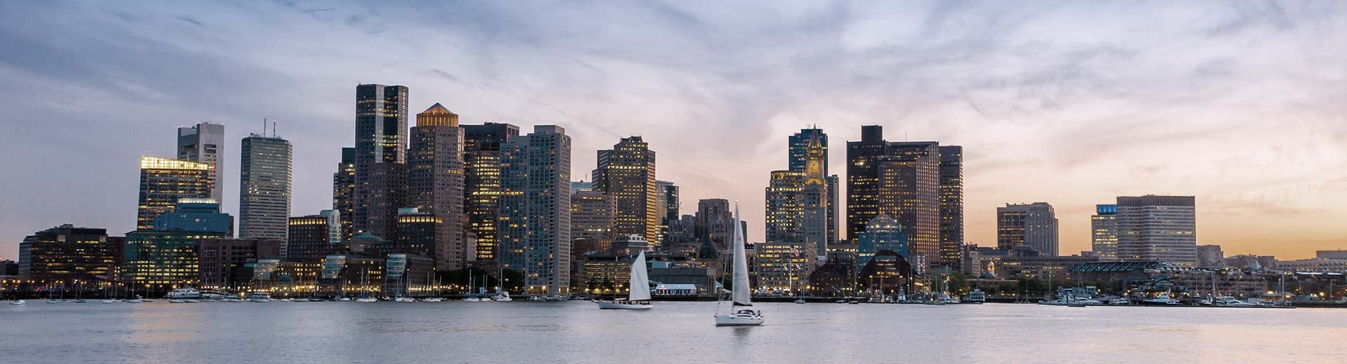 Panorama shot of the Boston business center at sunset from across the harbor