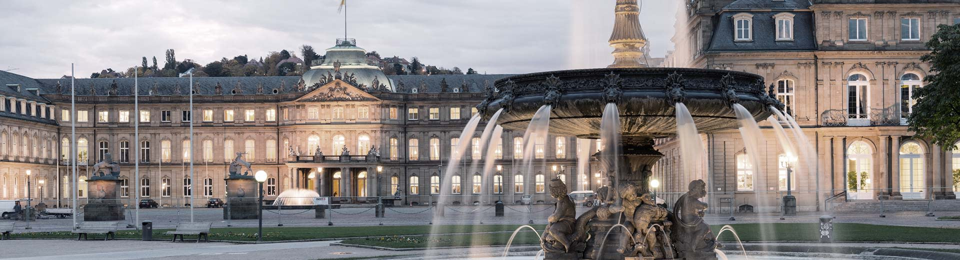 A beautiful fountain dominates the foreground, while behind stands a historic building in the half-light