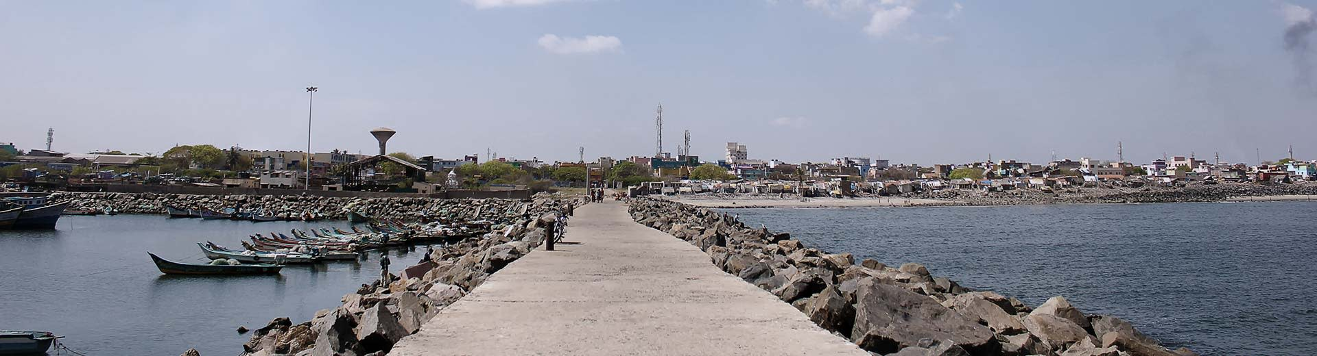 A simple stone pier in Chennai, lined with small boats on a clear and sunny day
