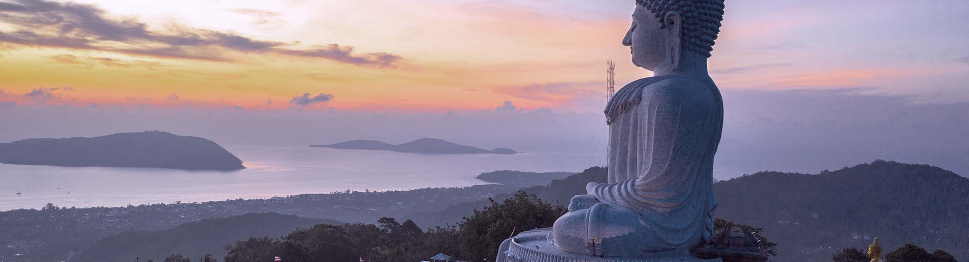 A religious statue sits on top of a hill, overlooking a coastline in the half-light of dusk