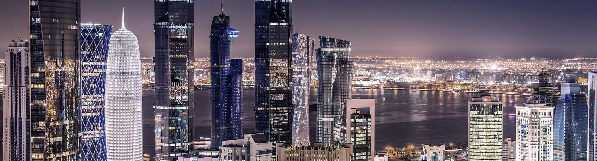 The varied and imposing skyscrapers of Doha pierce the nightsky