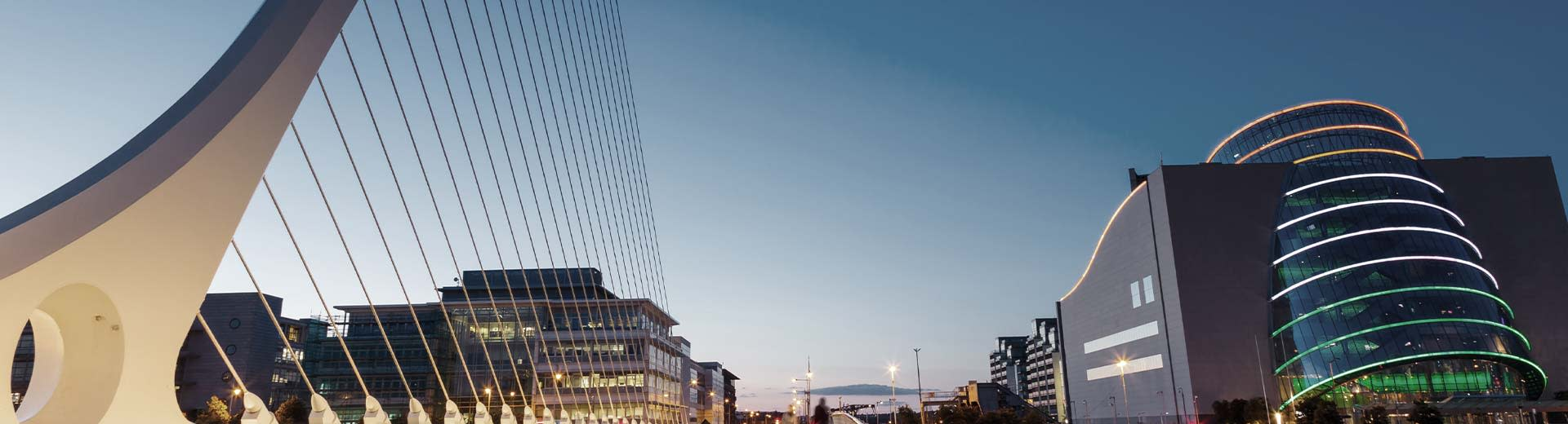 Commercial buildings and a modern bridge during a darker part of the day in Dublin
