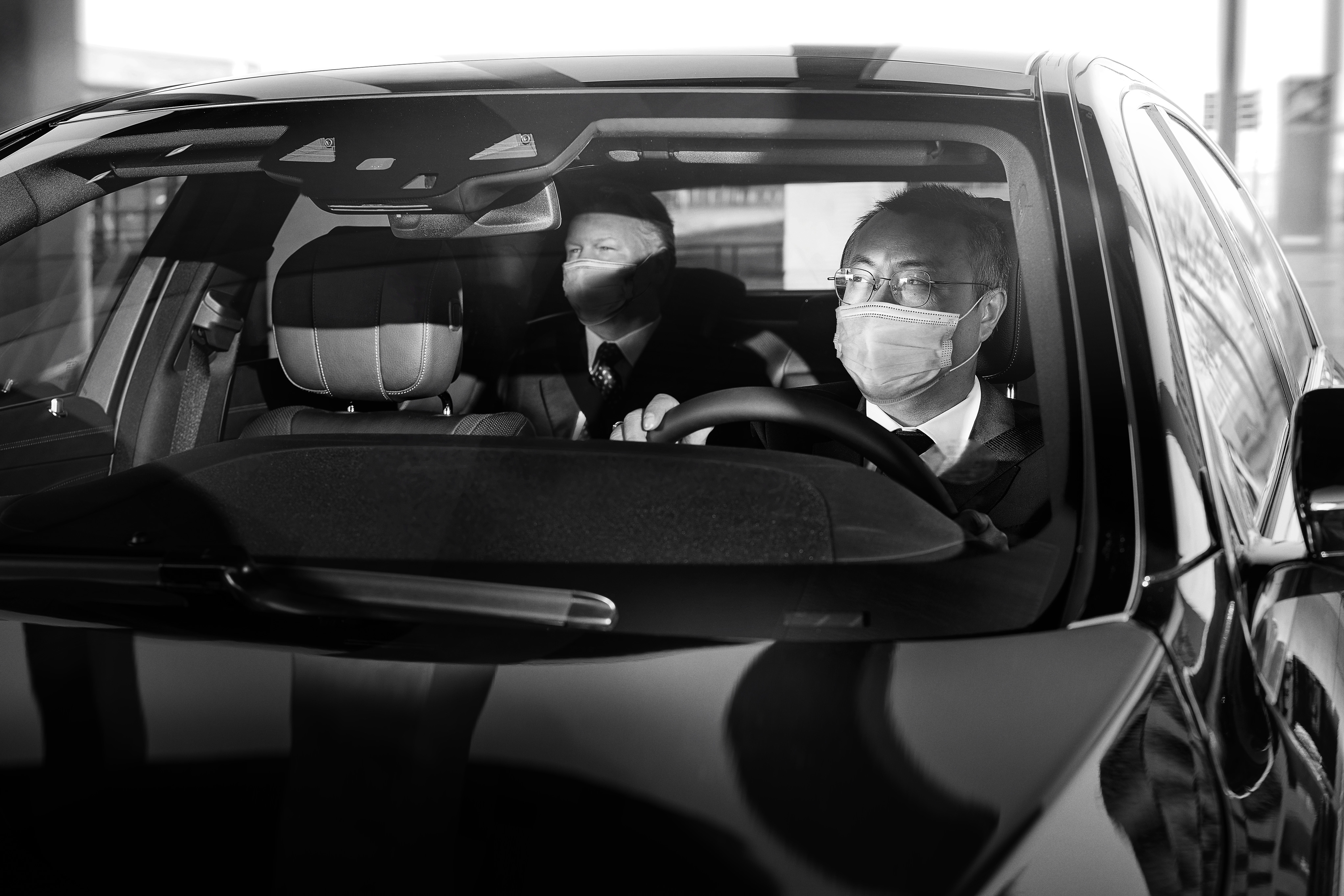 Chauffeur and guest in car with masks