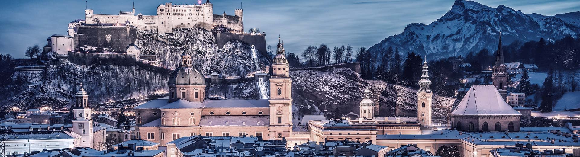 Salzburg Castle lights up the night sky in the background, while historic buildings are visible to the fore