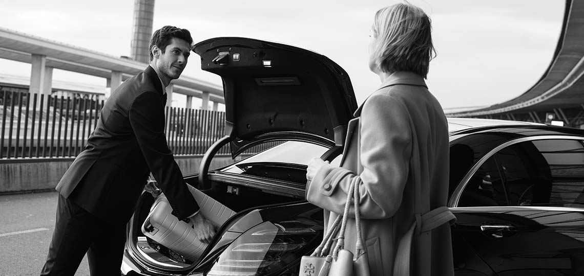 Blacklane chauffeur helping female passenger put her luggage into the trunk of the vehicle