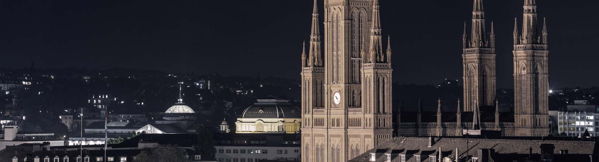 The world-famous Marktkirche dominates the foreground of Wiesbaden, with the lights of buildings in the distance