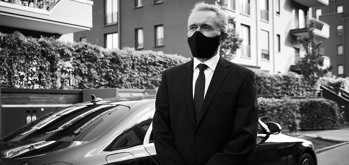 A chauffeur in a black suit stands outside his vehicle wearing a protective face mask.