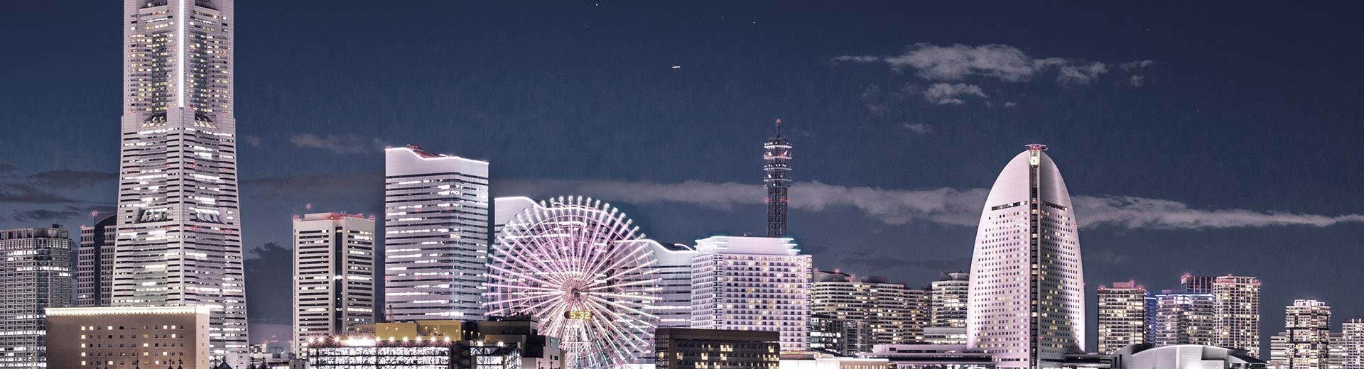 A row of modern skyscrapers at night in Yokohama light up the dark, with an irreverent Ferris Wheel in the foreground