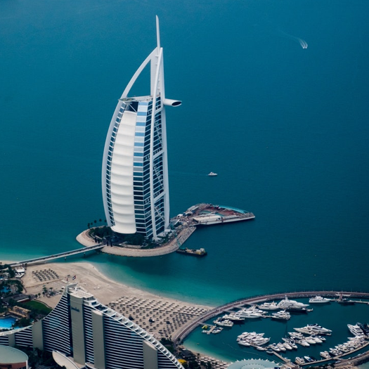 The Burj Al Arab Hotel in Dubai is shaped like the sail of a boat and surrounded by ocean water.