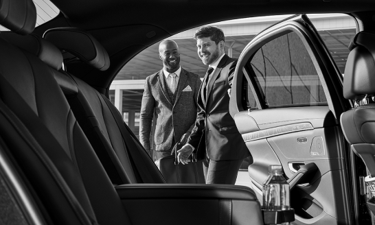 Douglas, a real Blacklane chauffeur, opens the car door for a guest.