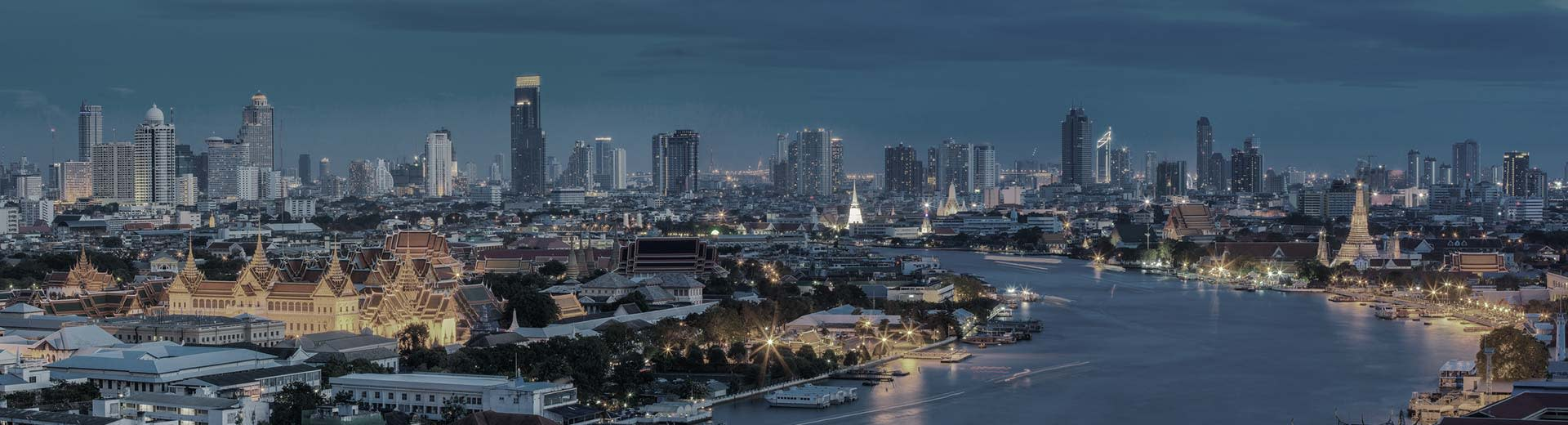 View of Bangkok skyline on a clear evening with the city lights creating a glow.