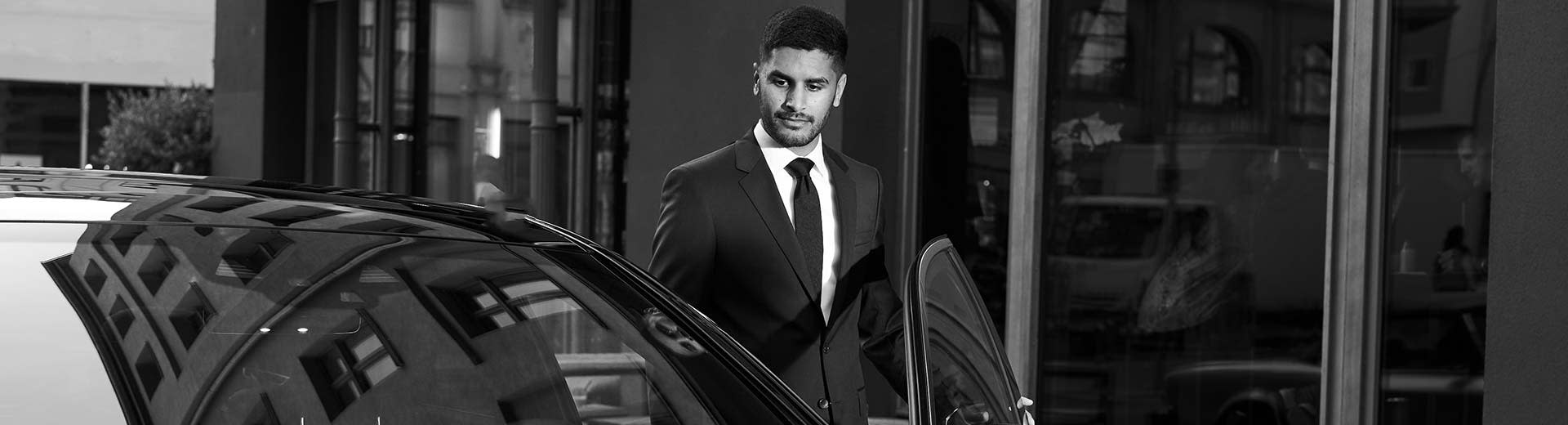 Umair, a real Blacklane chauffeur in Stuttgart, stands in a suit and tie behind his black car, ready to drive his guest.