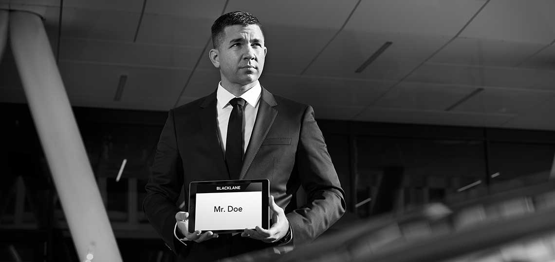 A Blacklane chauffeur in a black suit and tie waits outside arrivals with a tablet pickup sign saying Mr. Doe.