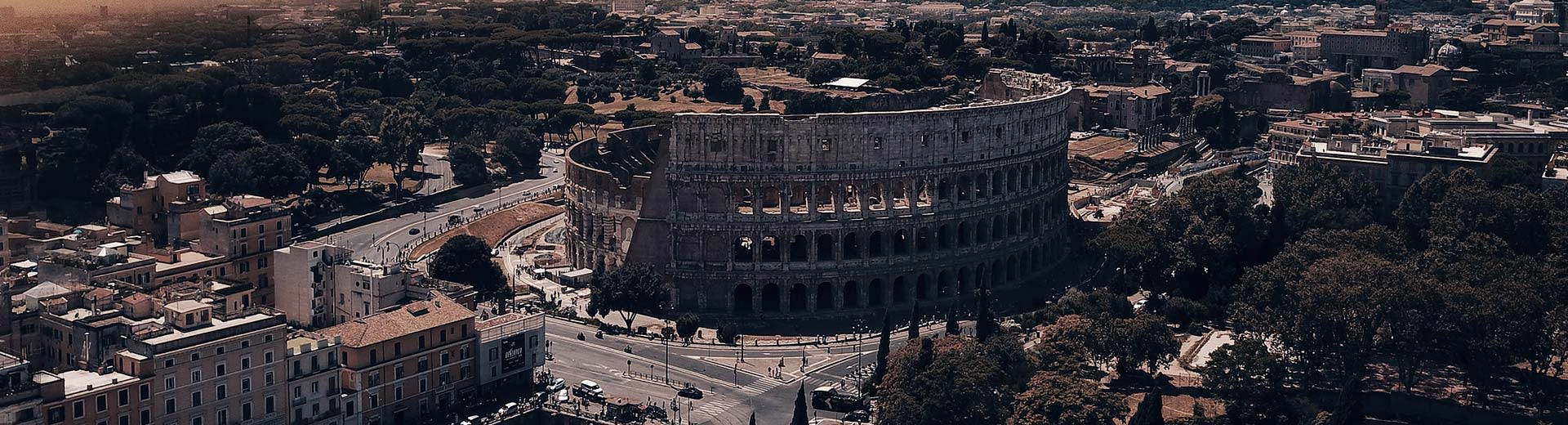 In the half-light of dusk or dawn, the famous Colosseum of Rome dominates the image, surrounded by buildings