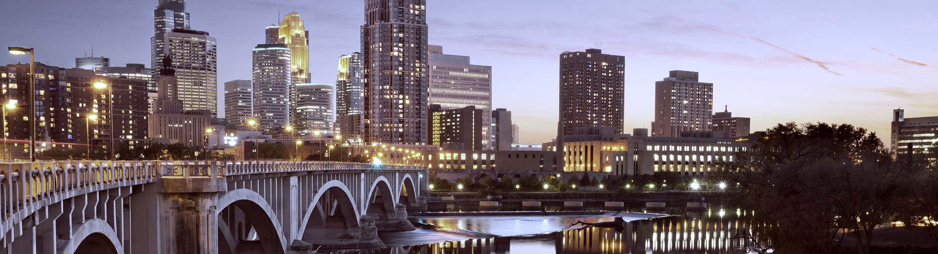 A bridge and high-rise skyscrapers light up the sky above Minneapolis