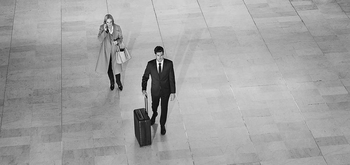 Blacklane chauffeur assisting a passenger through the airport by wheeling her luggage