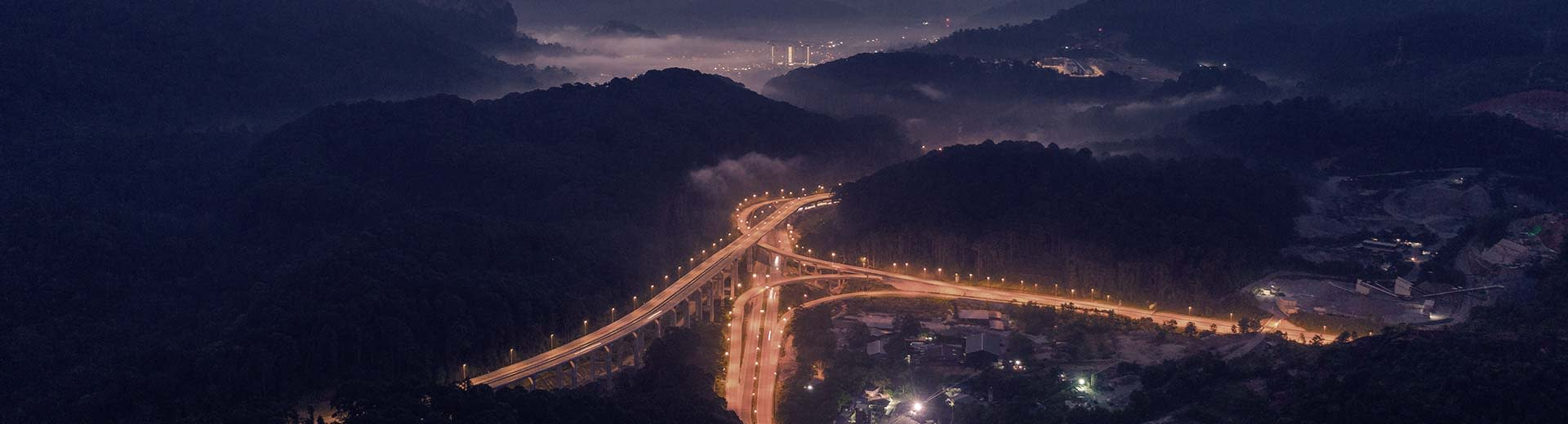 Dark hills suround a brightly lit highway, with the lights of Rawang in the distance
