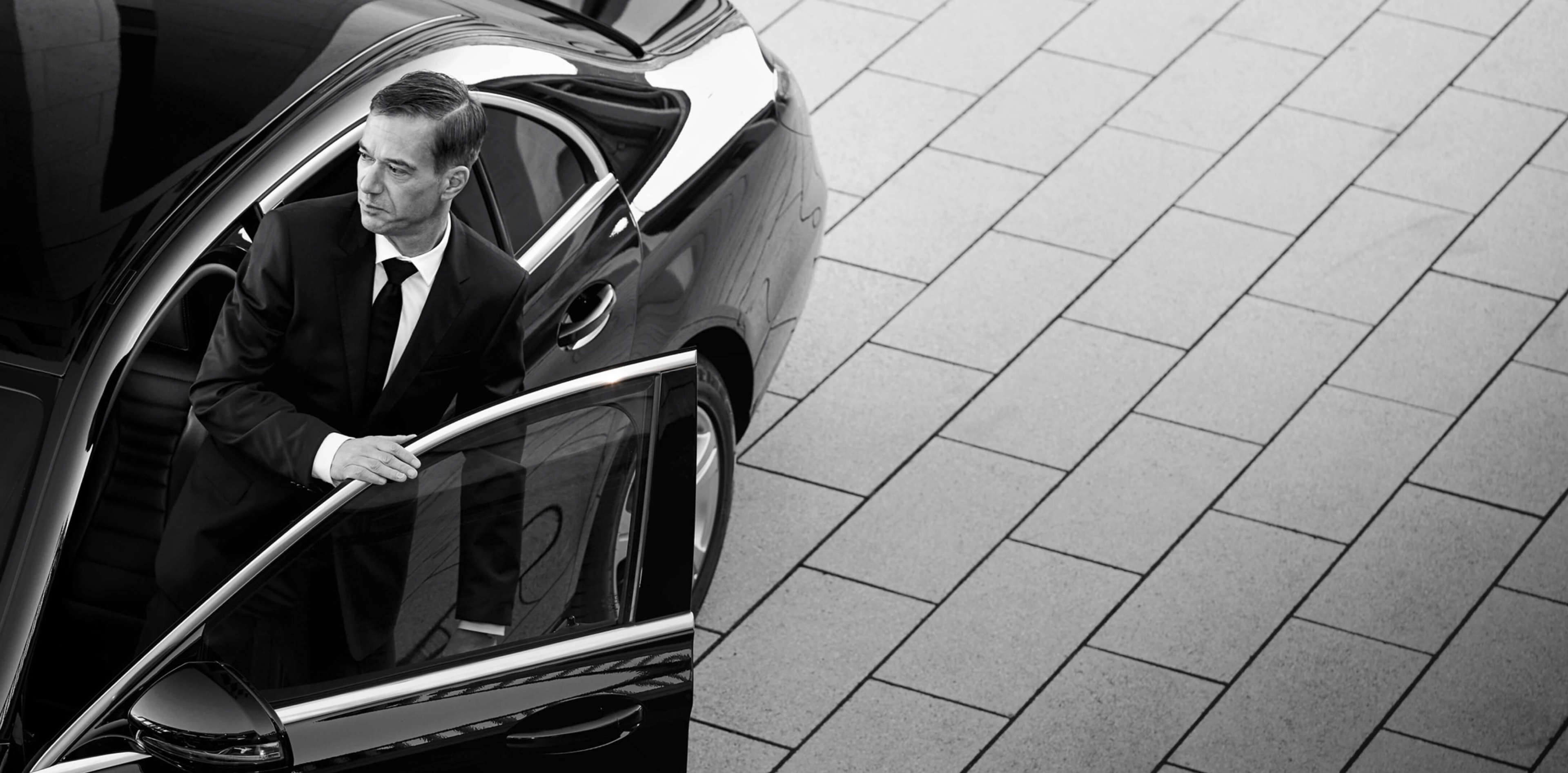 Real Blacklane chauffeur Peter rests his hand on the door of his spotless Mercedes, ready to get into the driver's seat.