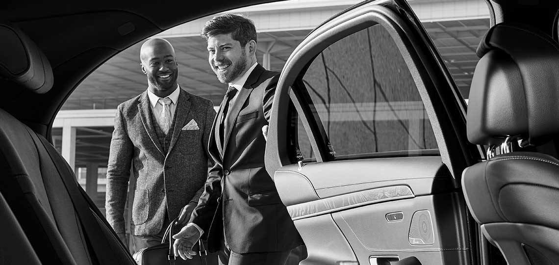 Real Blacklane chauffeur Douglas shares a laugh with his guest as he opens the backdoor of his Mercedes for them.