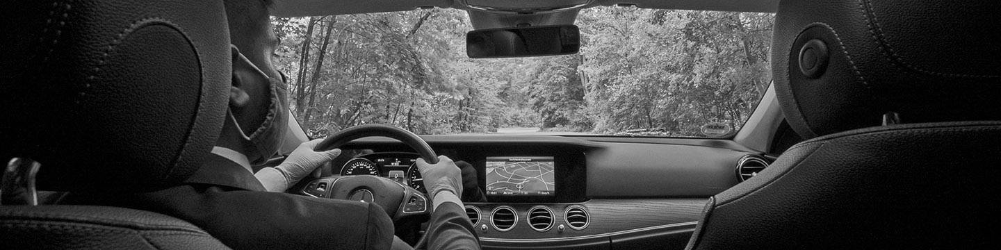 The view from the backseat of a high-class car, including a chauffeur wearing a mask, the high-tech dashboard, and the tree-lined road ahead.
