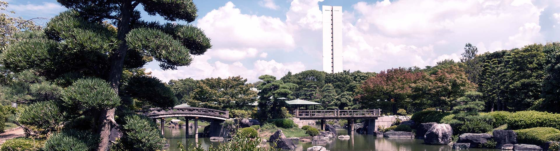 A traditional, green Japanese garden dominates the image, with a single white building looming in the background
