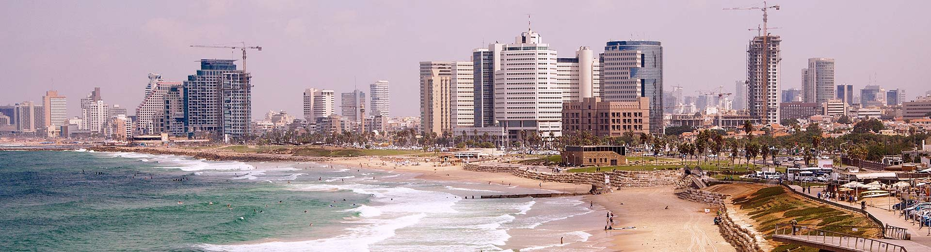 Under a cloudy Tel Aviv sky lie some generic looking skyscrapers and hotels, while a nearly empty beach is in the foreground