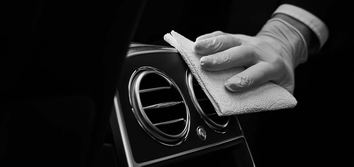 A chauffeur's gloved hand wipes down the interior of a car with disinfectant.