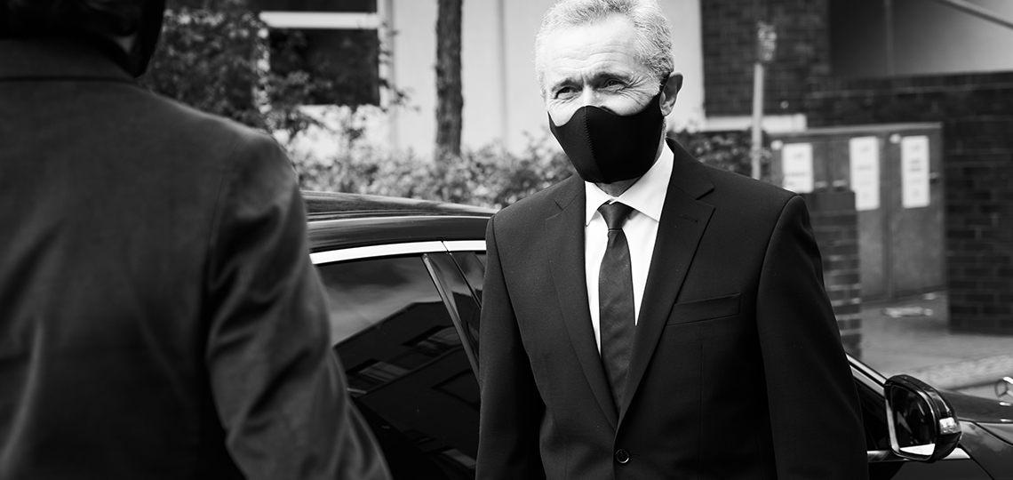 A chauffeur wearing a protective face masks gets ready to greet an approaching guest.