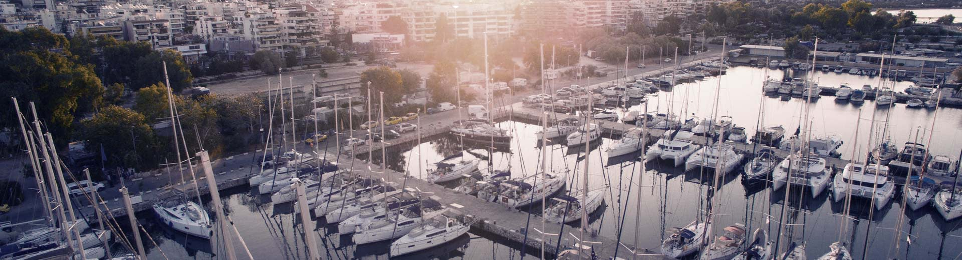 On a harbour in Piraeus, a number of private yachts lie in wait on a hot and clear day