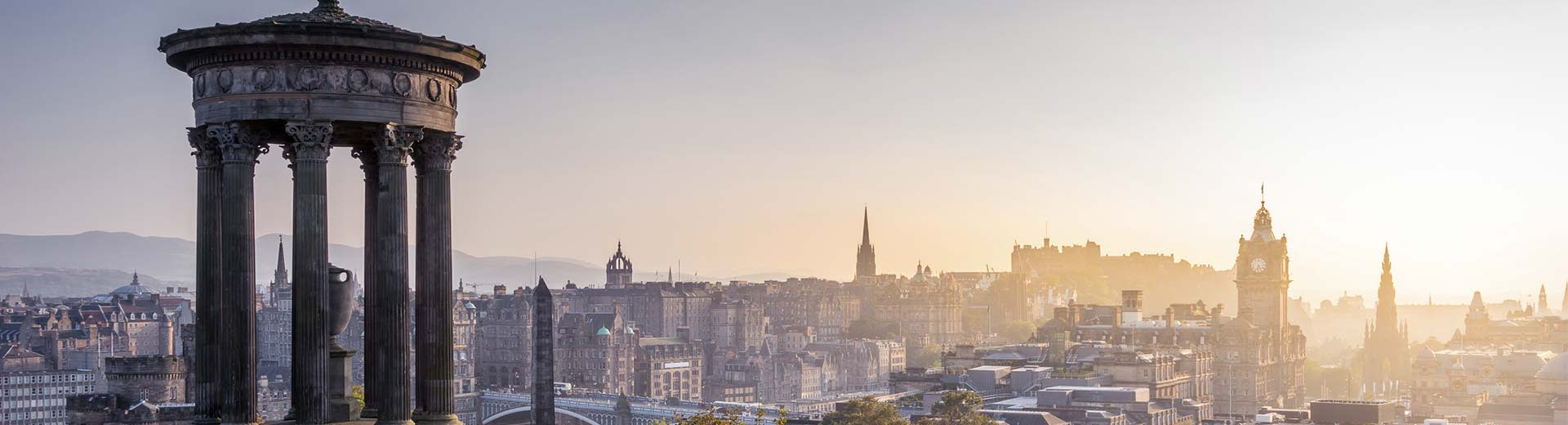 The sun pierces the sky over the skyline of Edinburgh