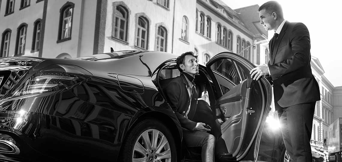Real Blacklane chauffeur Vince opens the door of his Mercedes to let a guest out of the backseat.