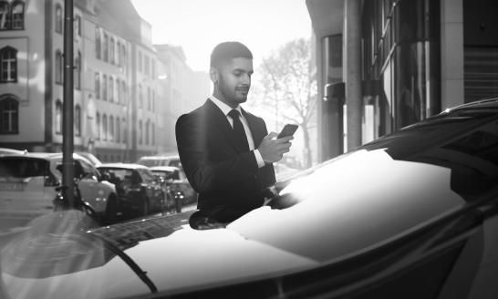 Umair, a real Blacklane chauffeur, looks at his phone while waiting outside a vehicle.