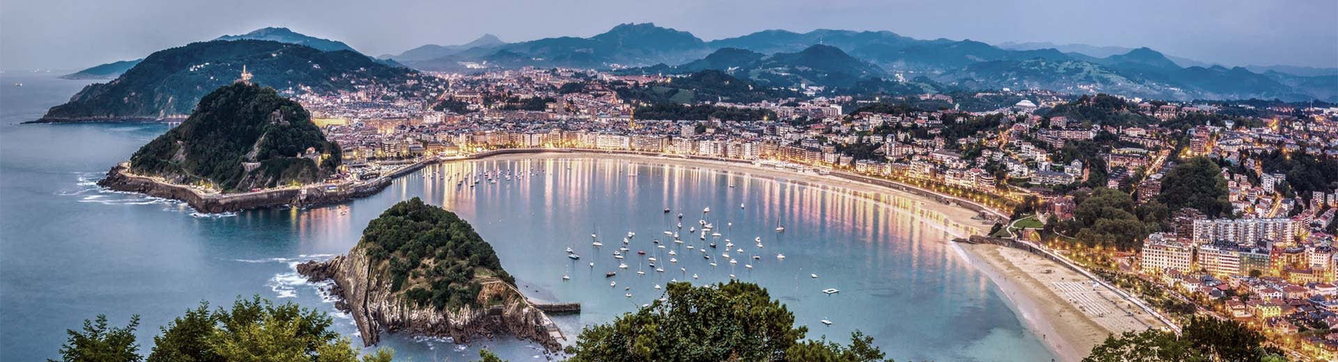 One of the beautiful beaches of San Sebastian, with buildings along the coast lighting up the dusk sky