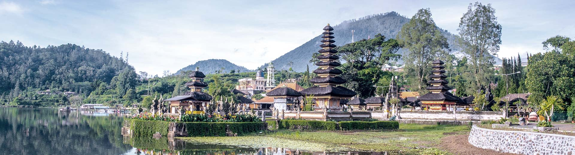 Ulun Danu Beratan Temple in Bali alongside the calm Beratan lake with mountains in the background