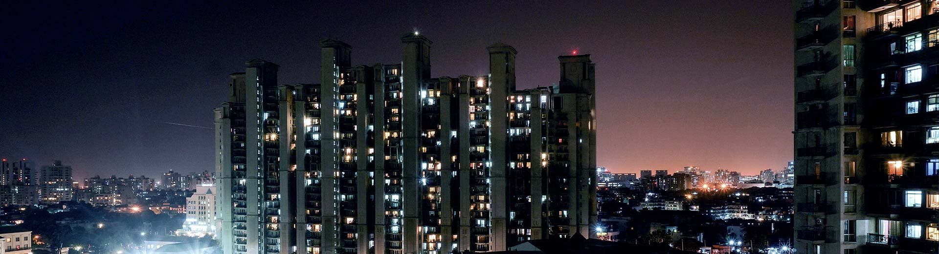 High-rise residential buildings light up the night sky in Gurgaon