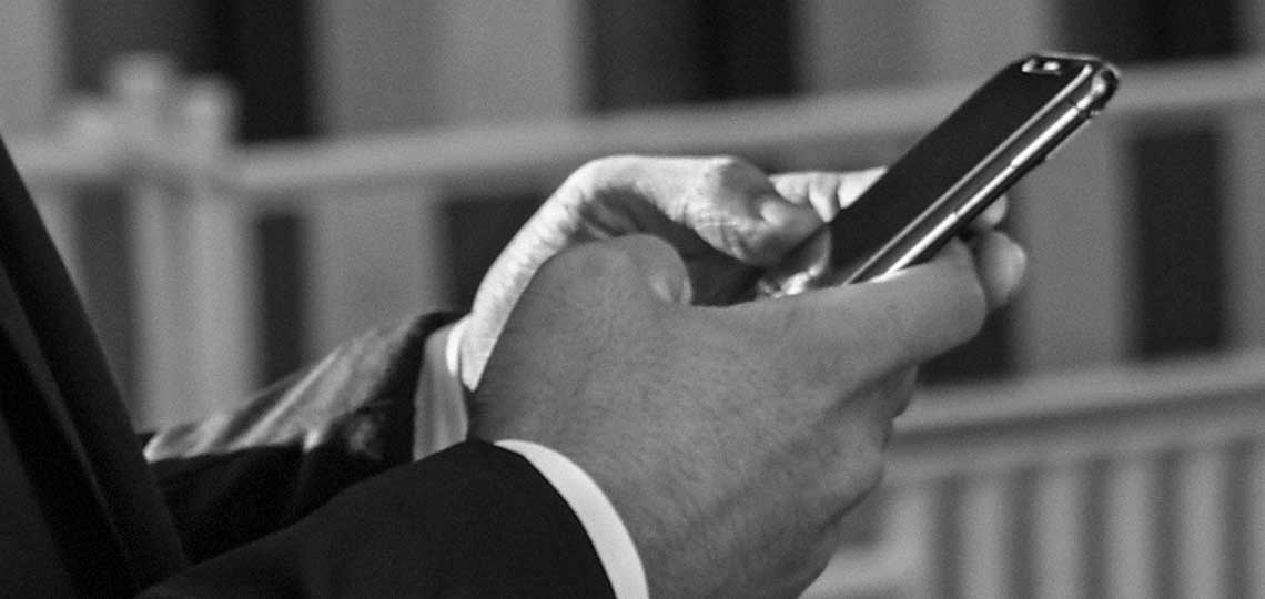 A man in a nice suit holds a smartphone with both hands, using the app to book a ride in advance.