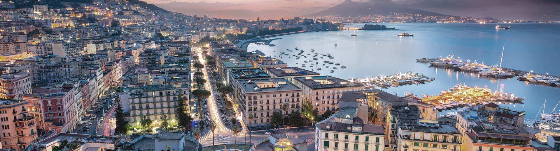 The beautiful city of Naples stretches across the coast at dusk